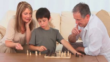 Grandmother helping her grandson to play chess against the grandfather