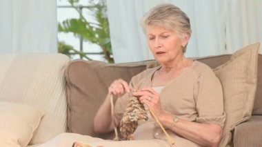 Mature woman knitting on the sofa
