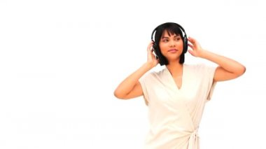 Casual asian woman listening to music with headphones against a white background