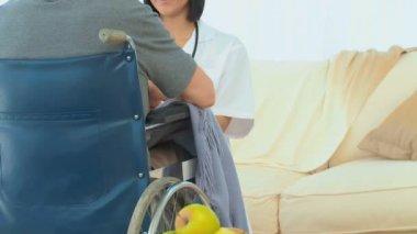 Pacjent w wózku rozmowy z jego pielęgniarka — Wideo stockowe