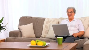 Mature woman laughing in front of her laptop — Stock video