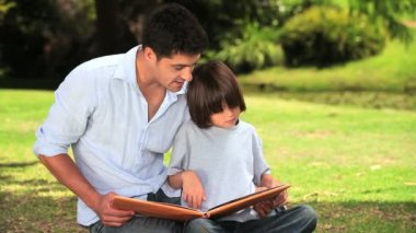 Father and son sitting reading outdoors — Stock Video