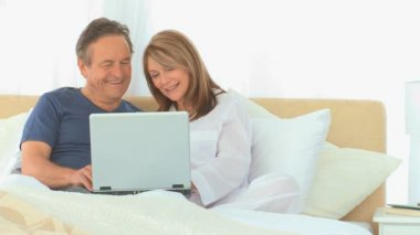 Retired couple using a laptop in the bed