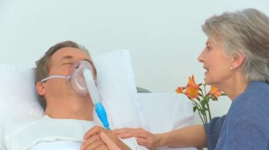 Elderly woman talking to her unconscious husband — Stock Video