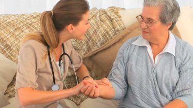Nurse taking the pulse of her patient at home — Stock Video