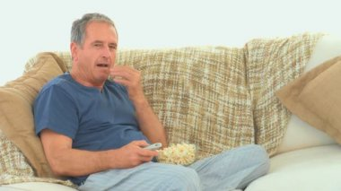 Mature man watching tv with popcorn — Wideo stockowe