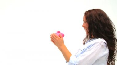 Woman with her piggy bank against a white background — Stock Video