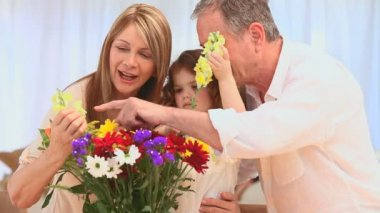 Family putting on flowers in a vase in the living room