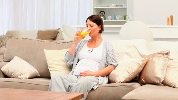 Mujer morena embarazada beber un vaso de jugo de naranja — Vídeo de stock