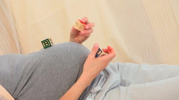 Mujer embarazada jugando con bloques de construcción — Vídeo de stock