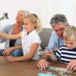 Royalty-Free Stock Imagem Vetorial: Grand parent playing with their grandson and grand-daughter
