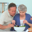 Mature couple preparing a salad — Stock Video #15540275