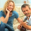 Casual playing guitar next to his wife - Stock Photo