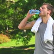 Stock Video: Dark haired mwith bottle of water and towel