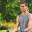 Stock Video: Handsome mdoing exercises with dumbbells