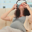 Woman putting headphone on her belly - Stock Photo