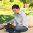 Stock Video: Womreading book in park