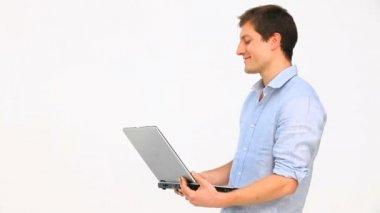 Ung man står upp med en bärbar dator — Stockvideo