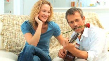 Toevallige spelen gitaar naast zijn vrouw — Stockvideo