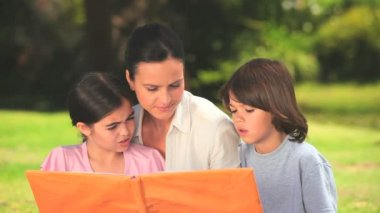 Mother outdoors with her children looking at a book — Stock Video