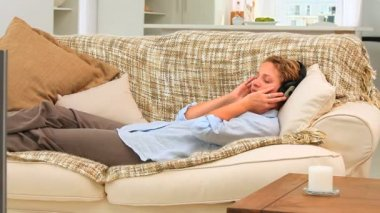 Woman lying and listening to music — Stok video