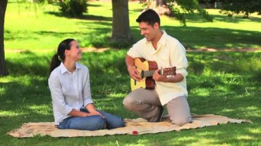 Attractive man playing guitar to his wife — Stock Video