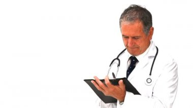 Mature doctor taking notes — Stock Video