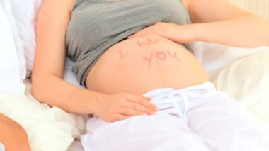 "Pregnant woman sitting on her bed with I love you"" written on her belly"""