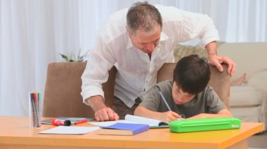 Grandfather helping his grandson to do homeworks — Stock Video