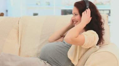 Pregnant woman putting her earphone on her belly