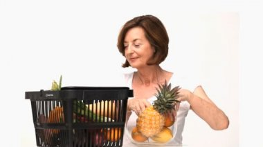 Mature woman putting fruit into a bowl isolated on a white background