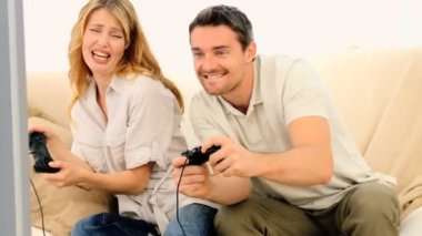 Cute couple playing a video game with with two joysticks — Stock Video