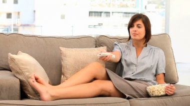 Casual brunette woman watching tv with popcorn — Stock Video