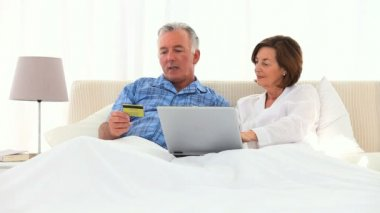 Elderly couple using a credit card on the internet — Stock Video