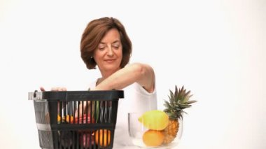 Senior woman putting fruit into a bowl — Stock Video