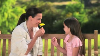 Mother and daughter playing with a flower — Stock Video
