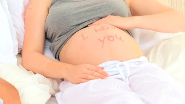 Mujer embarazada sentada en su cama — Vídeo de stock