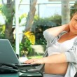 Tired woman working on her laptop - Stock Photo