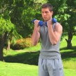 Stock Video: Handsome male doing musculation exercises