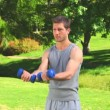 Stock Video: Handsome musing dumbbells outdoors