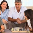 Parents looking at their children playing chess - Stock Photo
