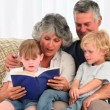 Grandparents reading a book to their grandchildren - Foto Stock