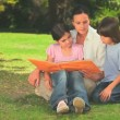Royalty-Free Stock Vektorfiler: Mother reading to her children