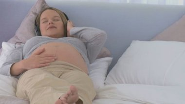 Pregnant woman sleeping with headphones on her bed
