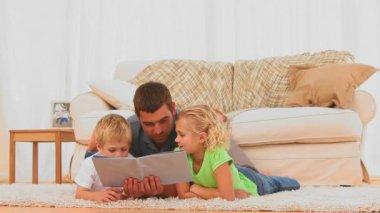 Pai atencioso, lendo uma crianças para reservar para seus filhos — Vídeo Stock
