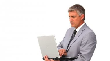 Middle aged man in suit standing with a laptop — Stock Video
