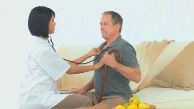 Asian nurse listening to heartbeat — Stock Video