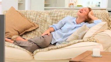 Mulher casual, rindo em frente a tv — Vídeo Stock