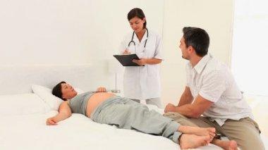 Cute nurse visiting a pregnant patient — Stock Video
