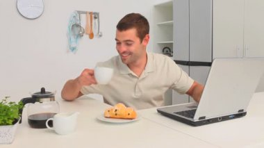 Man drinking a cup of coffee while he is working on his laptop — Stock Video